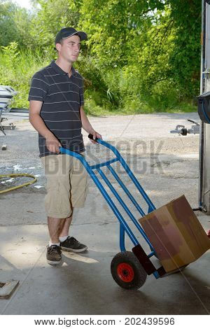 A young employee carries a package with handtruck