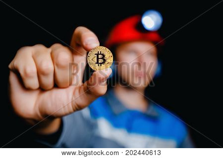 Miner holds gold bitcoin. Concept of production of crypto currency, mining cryptography.