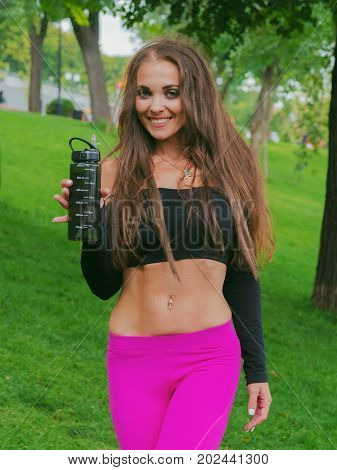 Thirsty female jogger drinking fresh water after training. Young athletic woman exercising in the park outdoors.