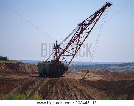 Side view of an industrial moving machine in the foundation pit. Huge mobile crane working in the sandy quarry. Industry equipment on a blue sky background. Technology, cargo, transport concept.