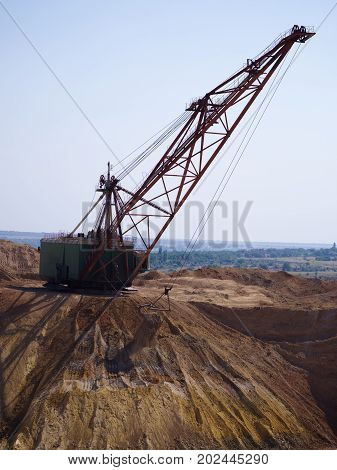 A close-up of an industrial moving machine in the foundation pit. Huge mobile crane working in the sandy quarry. Industry equipment on a blue sky background. Technology, cargo, transport concept.