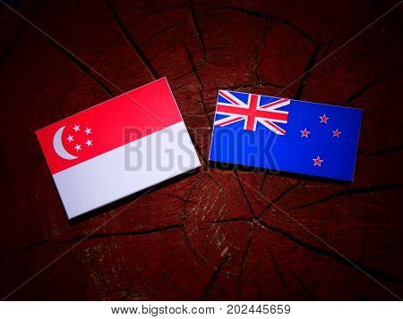Singaporean Flag With New Zealand Flag On A Tree Stump Isolated