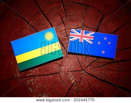 Rwanda Flag With New Zealand Flag On A Tree Stump Isolated