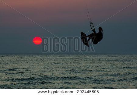Kite boarding. Kitesurf freestyle at sunset. Woman kitesurfer