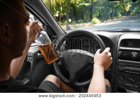 A young driver with a bottle of beer or whiskey on a blurred car background. A boozed young adult in casual clothes driving an automobile. Alcohol intoxication and addiction concept.