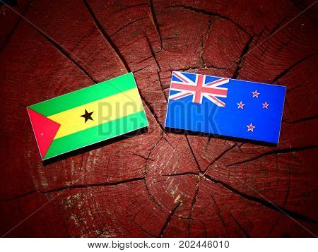 Sao Tome And Principe Flag With New Zealand Flag On A Tree Stump Isolated