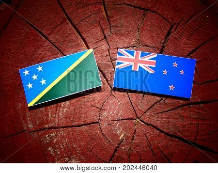 Solomon Islands Flag With New Zealand Flag On A Tree Stump Isolated