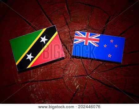 Saint Kitts And Nevis Flag With New Zealand Flag On A Tree Stump Isolated