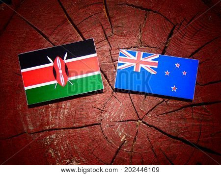 Kenyan Flag With New Zealand Flag On A Tree Stump Isolated