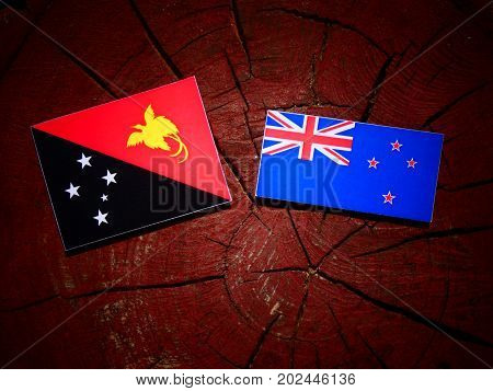 Papua New Guinea Flag With New Zealand Flag On A Tree Stump Isolated
