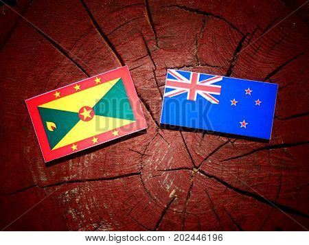 Grenada Flag With New Zealand Flag On A Tree Stump Isolated