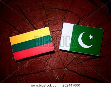 Lithuanian Flag With Pakistan Flag On A Tree Stump Isolated