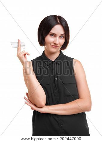 A confident, sassy young brunette woman holding many cigarettes isolated over the white background. A problematic female student with harmful nicotine addiction, in a dark casual shirt.
