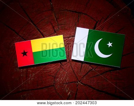 Guinea Bissau Flag With Pakistan Flag On A Tree Stump Isolated