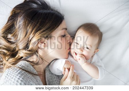 A Mother and baby child on a white bed.