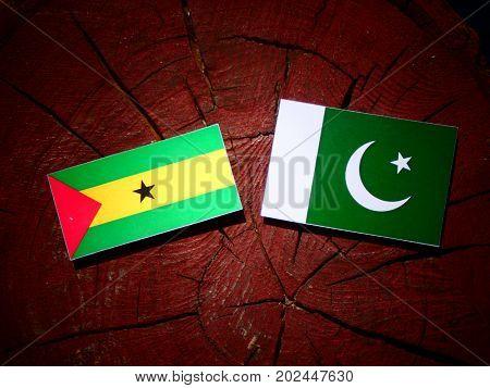 Sao Tome And Principe Flag With Pakistan Flag On A Tree Stump Isolated