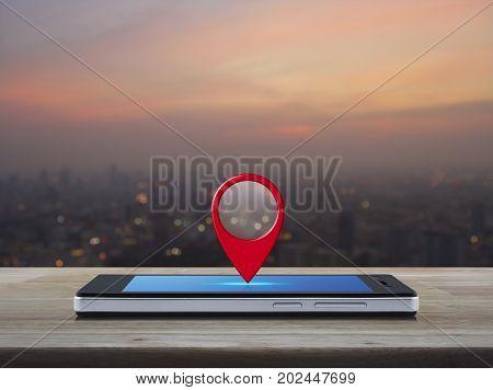Map pin location button on modern smart phone screen on wooden table over blur of cityscape on warm light sundown Map pointer navigation concept