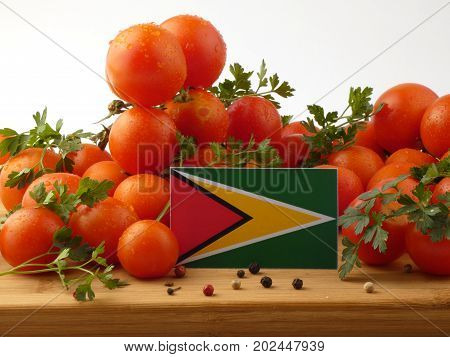 Guyana Flag On A Wooden Panel With Tomatoes Isolated On A White Background