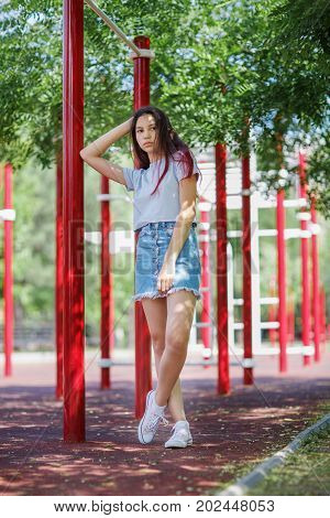 A full-length photo of a trendy young girl wearing a crop top and denim skirt on a blurred athletic field background. A beautiful adolescence lady posing in the outdoors. Youth, outdoors concept.