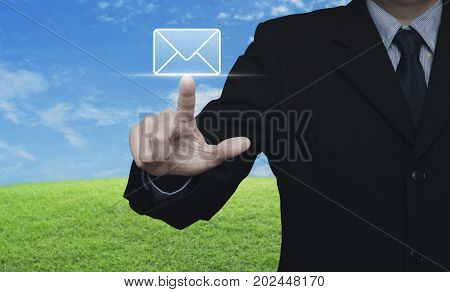 Businessman pressing mail flat icon over green grass field with blue sky Contact us concept