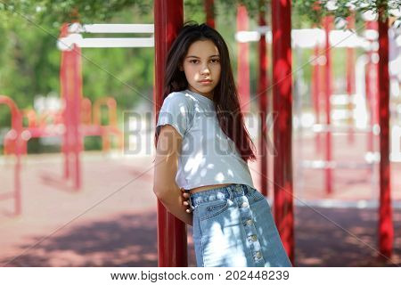 A close-up portrait of a tender young girl wearing a gray crop top and denim skirt on a blurred sports ground background. A beautiful adolescence lady posing outdoors. Youth, beauty, outdoors concept.