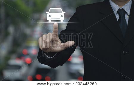 Businessman pressing car flat icon over blur of rush hour with cars and road Business transportation service concept
