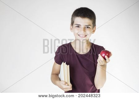 Portrait happy smiling boy holding books and red apple. Teenager smiling and looking at camera. Cheerful child holding books and apple. The concept of back to school.