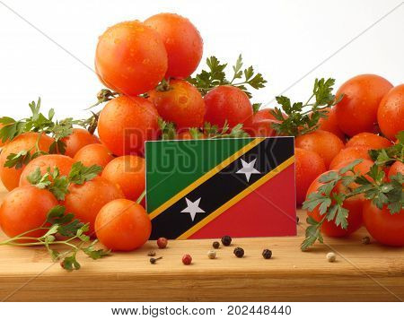 Saint Kitts And Nevis Flag On A Wooden Panel With Tomatoes Isolated On A White Background