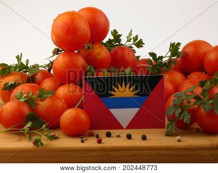 Antigua And Barbuda Flag On A Wooden Panel With Tomatoes Isolated On A White Background