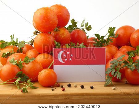 Singaporean Flag On A Wooden Panel With Tomatoes Isolated On A White Background