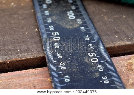 A ruler and a wooden shaving on boards of a light shade