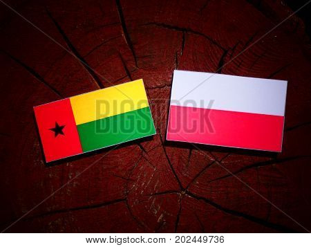 Guinea Bissau Flag With Polish Flag On A Tree Stump Isolated