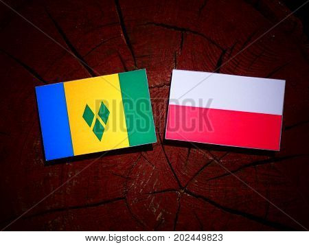 Saint Vincent And The Grenadines Flag With Polish Flag On A Tree Stump Isolated
