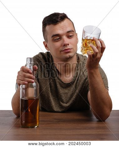 A drunk student in a khaki T-shirt sitting at the wooden table. A young relaxed guy looking at a transparent glass full of icy whiskey isolated on a white background. Alcoholism concept. Copy space.