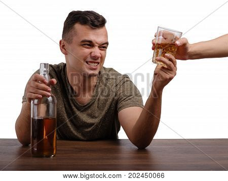 A drunk student in a khaki T-shirt struggling for a glass of an alcoholic beverage. A young boozed guy with a bottle and a transparent glass full of icy whiskey isolated on a white background.