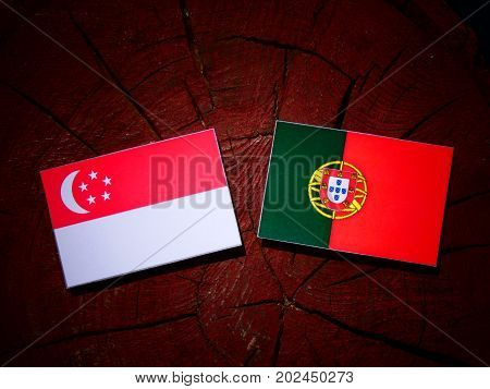 Singaporean Flag With Portuguese Flag On A Tree Stump Isolated