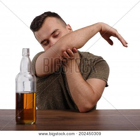 A young drunk guy with an alcohol overdose isolated on a white background. A sad boozed student in a khaki T-shirt with a raised hand sitting at the wooden table. Alcoholism concept. Copy space.