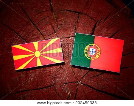 Macedonian Flag With Portuguese Flag On A Tree Stump Isolated
