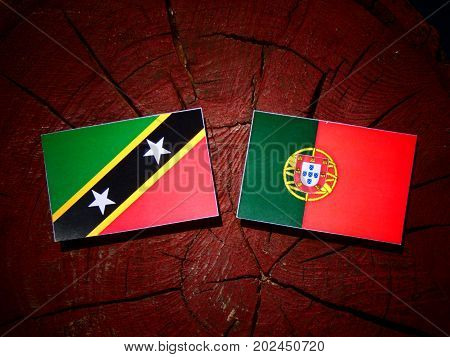 Saint Kitts And Nevis Flag With Portuguese Flag On A Tree Stump Isolated