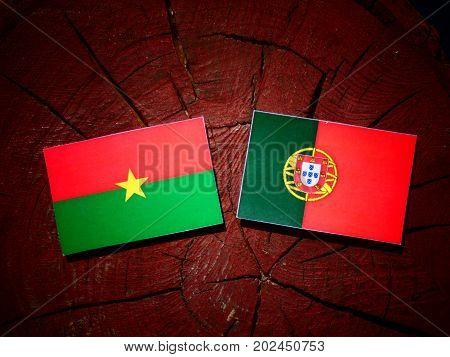 Burkina Faso Flag With Portuguese Flag On A Tree Stump Isolated