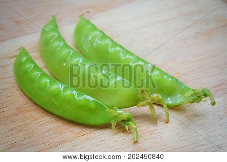 Vegetable Fresh Green Peas Pods on Cutting Board High in Vitamin K B C and A.