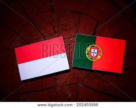Indonesian Flag With Portuguese Flag On A Tree Stump Isolated