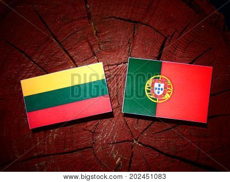 Lithuanian Flag With Portuguese Flag On A Tree Stump Isolated