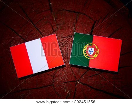 Peruvian Flag With Portuguese Flag On A Tree Stump Isolated
