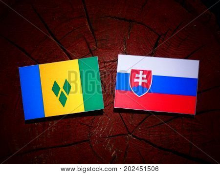 Saint Vincent And The Grenadines Flag With Slovakian Flag On A Tree Stump Isolated