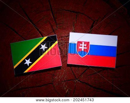 Saint Kitts And Nevis Flag With Slovakian Flag On A Tree Stump Isolated