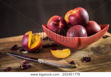 Ripe nectarines in a red plate. Style rustique.