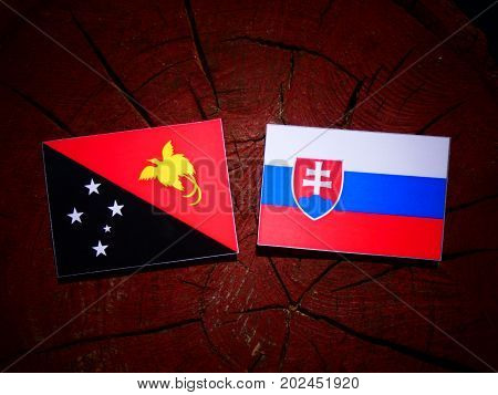 Papua New Guinea Flag With Slovakian Flag On A Tree Stump Isolated