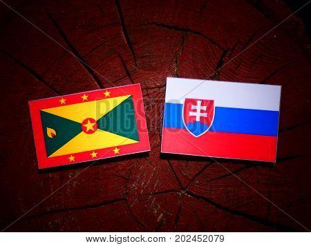 Grenada Flag With Slovakian Flag On A Tree Stump Isolated