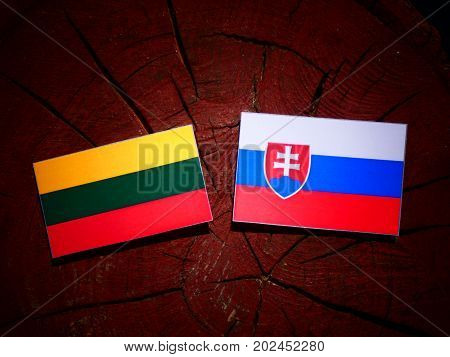 Lithuanian Flag With Slovakian Flag On A Tree Stump Isolated